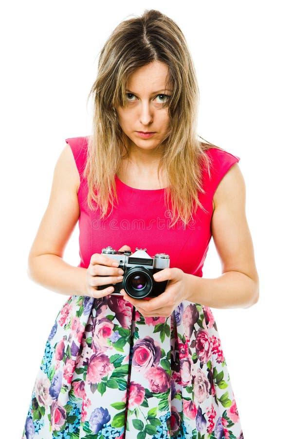 洋红色礼服的一位女性摄影师有葡萄酒模式照相机的-准备 库存照片