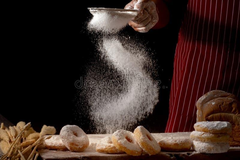 洒准备面团和多福饼与在黑背景隔绝的木桌上的糖粉的厨师手 免版税库存照片