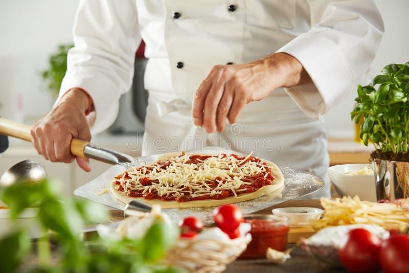 洒在一个未加工的薄饼上的厨师无盐干酪乳酪 库存照片