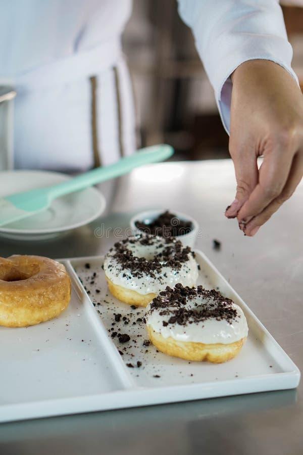洒在油炸圈饼的厨师 免版税图库摄影