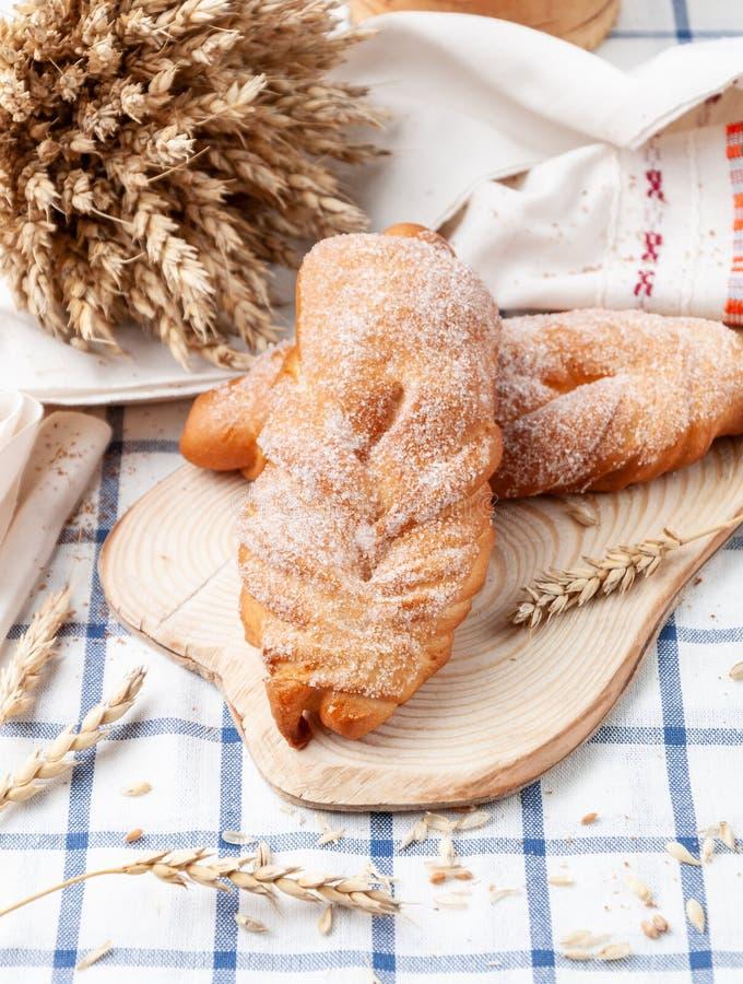 洒有糖的柳条自制面包 在木板上 蓝条白桌布 背景中,一颗小麦穗 免版税图库摄影