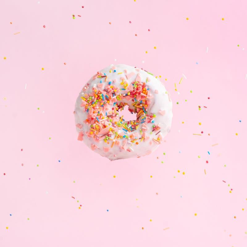 洒桃红色多福饼 在桃红色背景的一个多彩多姿的被洒的多福饼 库存图片