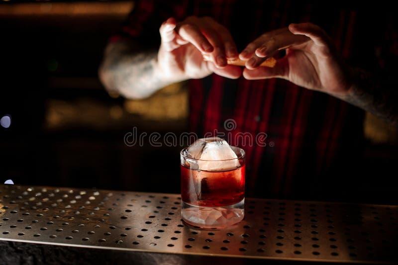 洒橙皮汁液的男服务员入鸡尾酒杯充满强的威士忌酒饮料 免版税库存图片