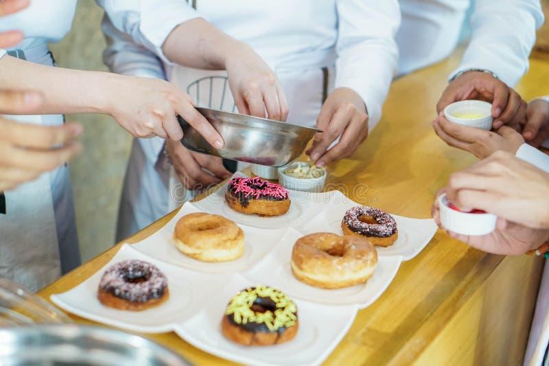 洒油炸圈饼的厨师与糖 免版税库存图片