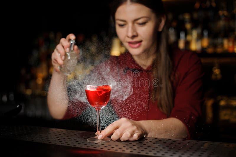洒鸡尾酒杯的微笑的女性男服务员用鲜美Aperol注射器夏天鸡尾酒填装了用peated威士忌酒 免版税库存图片