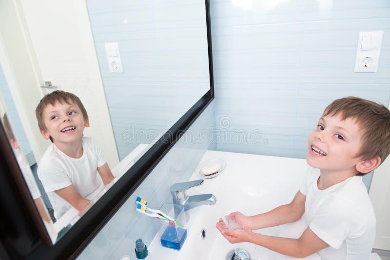 洗他的手的愉快的微笑的小孩在卫生间里 免版税库存图片