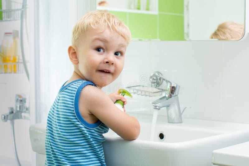 洗他的面孔和手有肥皂的儿童男孩在卫生间里 免版税库存图片