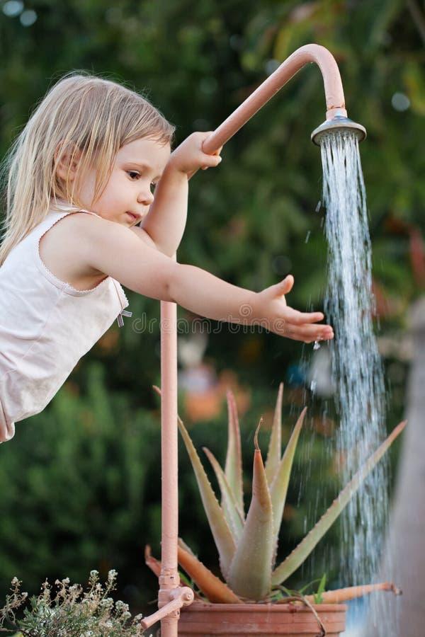 洗她的手的女孩室外 库存图片