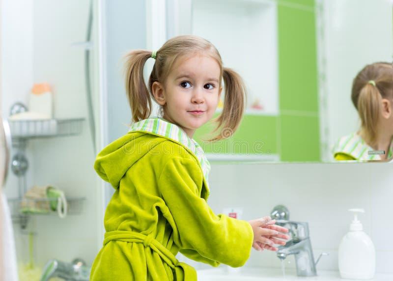 洗她的手的小女孩在卫生间里 免版税库存图片
