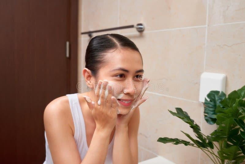 洗她的面孔用手的年轻美丽的亚裔妇女由肥皂 库存照片