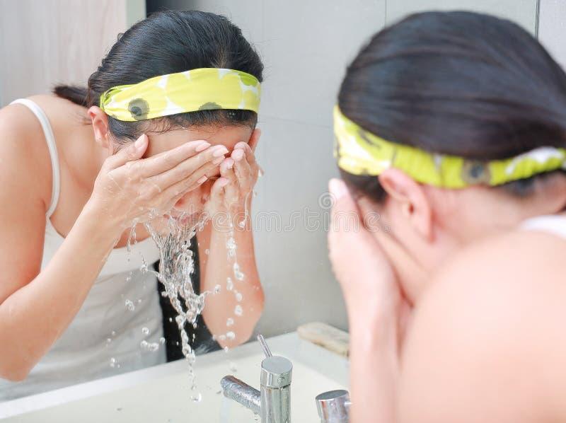 洗她的面孔的妇女清洁反射与卫生间镜子 库存照片