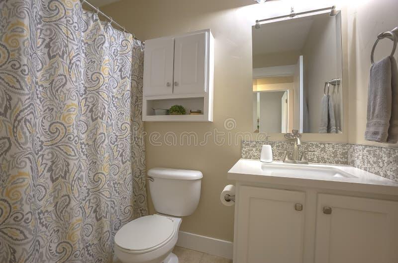 洗手间梳妆镜和内阁在卫生间里面有米黄墙壁和砖地的 库存图片