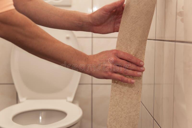 洗手间泪花手纸的妇女从卷 免版税库存图片