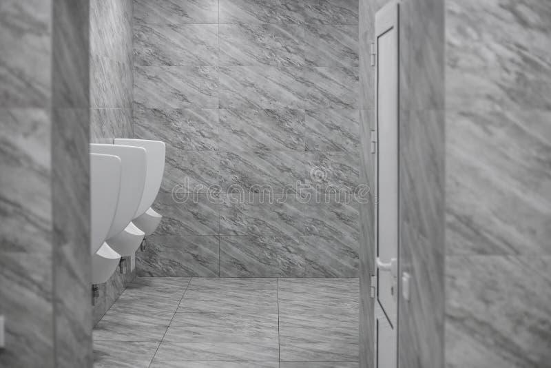 洗手间男盥洗室 室外尿壶人公共厕所,特写镜头白色尿壶接近的行在人的卫生间,白色设计里  免版税图库摄影