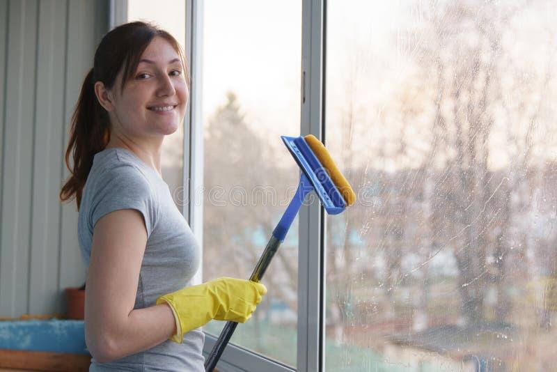 洗涤一个特别拖把的窗口和看照相机的黄色手套的少妇 免版税图库摄影