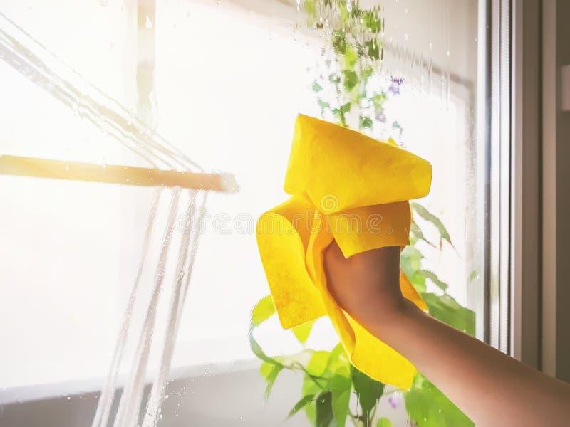 洗涤与旧布的年轻女人一个窗口 库存照片