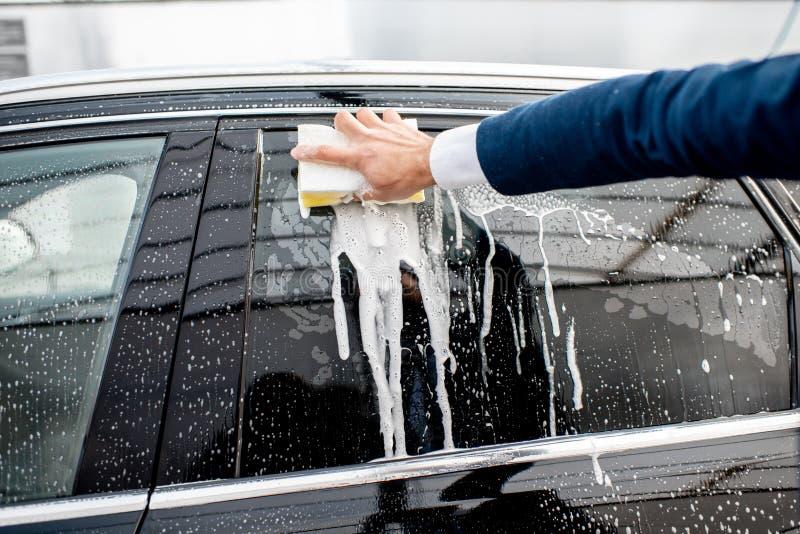 洗涤与海绵和泡沫的一个车窗 免版税库存图片