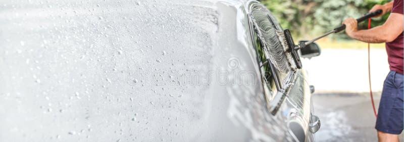 洗涤他的汽车的人在自已服务洗车,刷子清理玻璃复盖在香波 左边被扩展对横幅大小,空间 库存照片