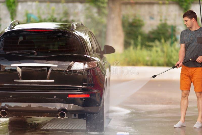 洗涤他的汽车的年轻人在洗车 库存图片