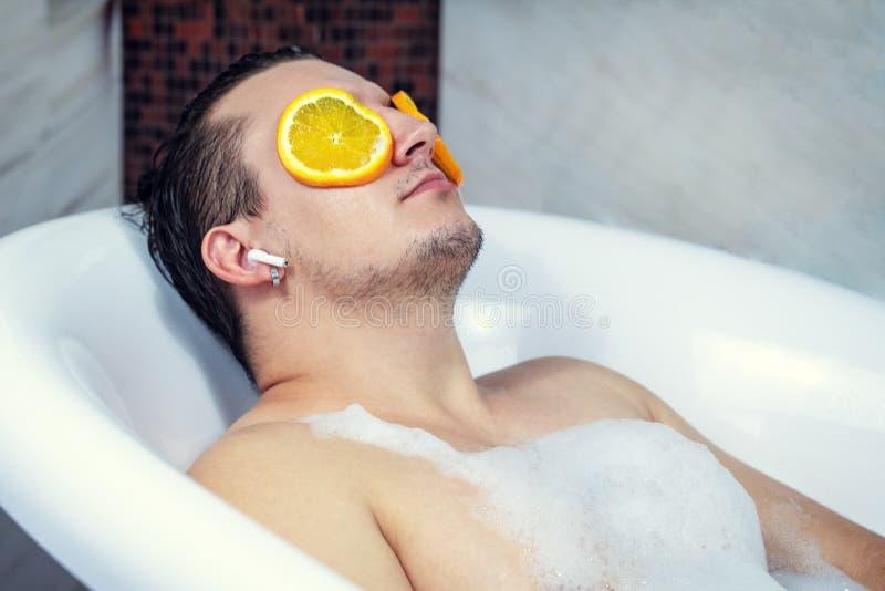 洗涤他的浴的滑稽的人 听到与无线耳机的音乐 放松从在面孔的温泉做法与橙色圆的切片 库存图片