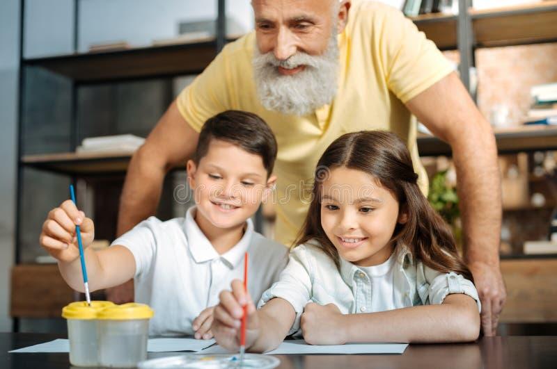 洗涤刷子和选择颜色的祖父观看的孙 免版税库存图片