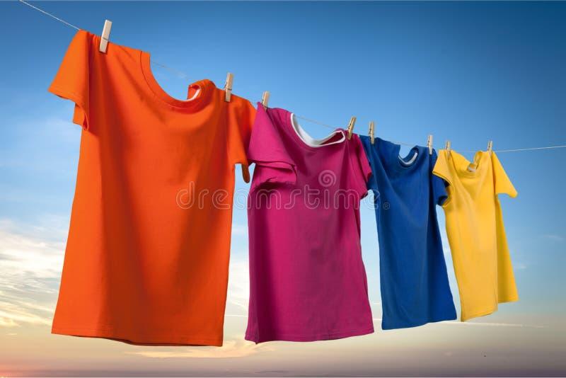 洗涤在一条绳索的衣裳与在日落的晒衣夹 免版税库存照片