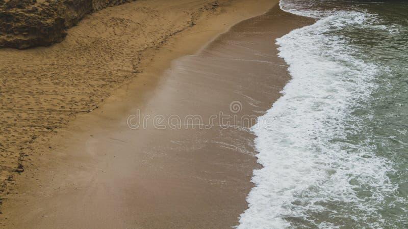 洗涤在海滩的波浪沙子在比亚利兹,法国 免版税库存图片