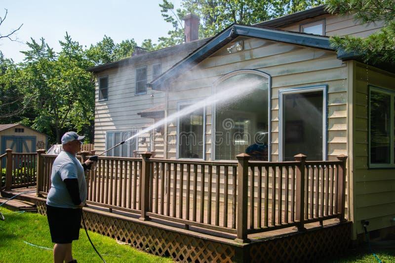 洗涤大窗口的重的丈夫力量在一个棕色木甲板的一个房子背面有压力洗衣机的 免版税库存照片