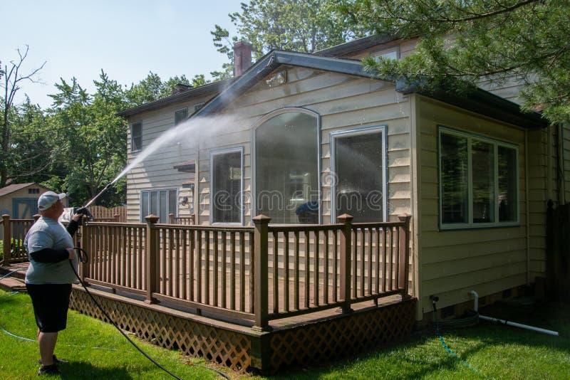 洗涤房屋板壁的重的丈夫力量在一个棕色木甲板的一个房子背面 免版税库存照片