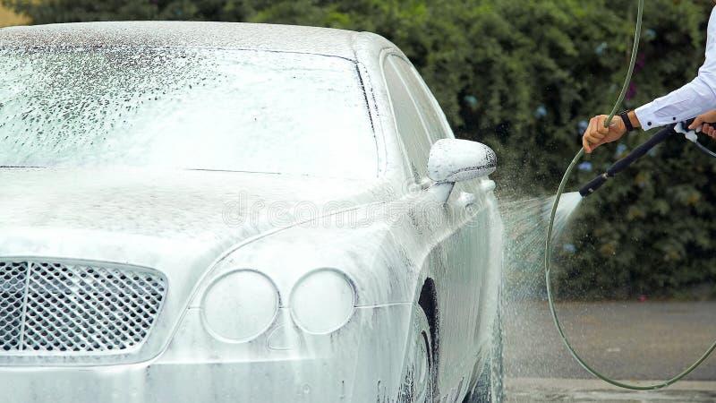 洗涤有suds的企业司机豪华汽车在采取上司前在工作 免版税图库摄影