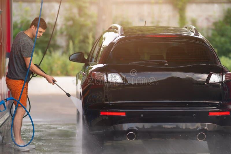 洗涤汽车的人使用高压系统 库存照片