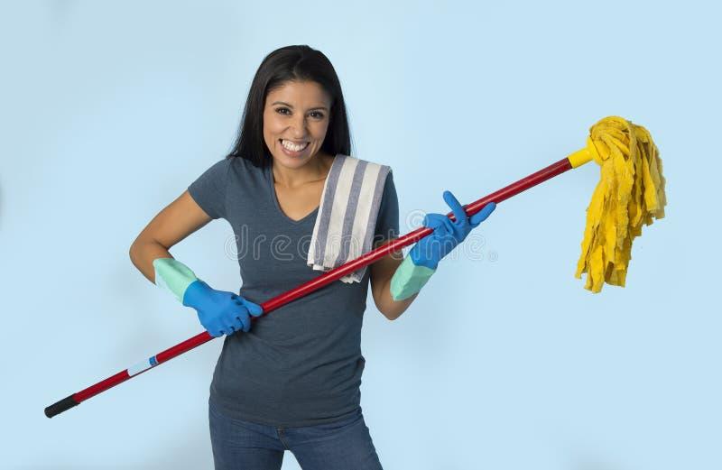 洗涤的手套的年轻可爱的愉快的拉丁妇女拿着拖把获得乐趣唱和演奏Air Guitar的激发 库存图片