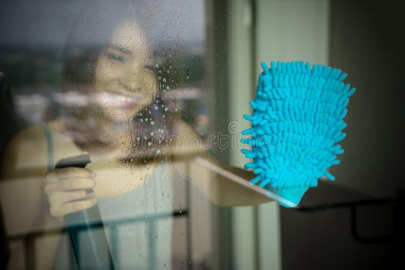 洗涤的视窗妇女年轻人 拿着瓶的手套的愉快的佣人 免版税图库摄影