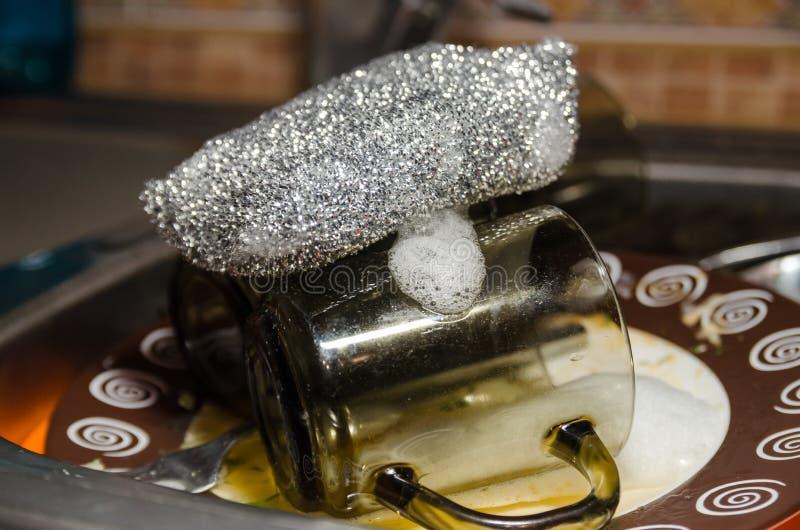 洗碗的海绵与肮脏的盘 免版税库存照片