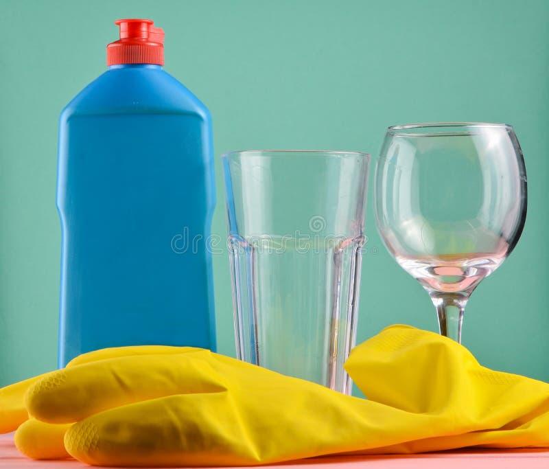 洗碗盘行为和房子清洁的辅助部件 洗碗盘行为 瓶在蓝色的洗涤剂,玻璃和黄色橡胶手套 库存照片