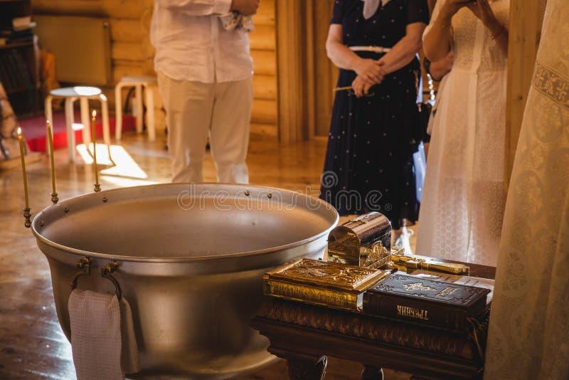 洗礼仪式仪式在东正教里,打开蜡烛在儿童洗礼盘,关闭的教士 免版税库存照片