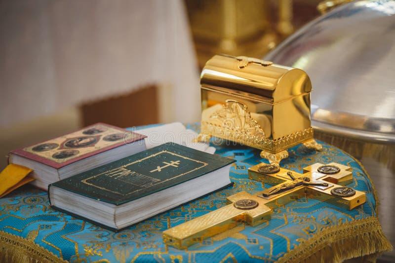 洗礼仪式在教会里,金黄宗教器物:圣经,十字架,祈祷书, missal 细节在正统基督教会里 图库摄影