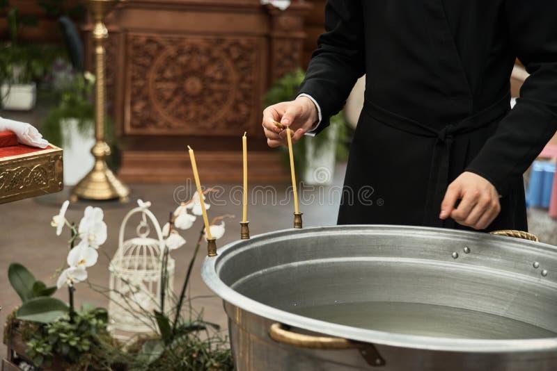 洗礼仪式在教会,教士点燃蜡烛在儿童洗礼盘 细节在正统基督教会里 免版税库存照片