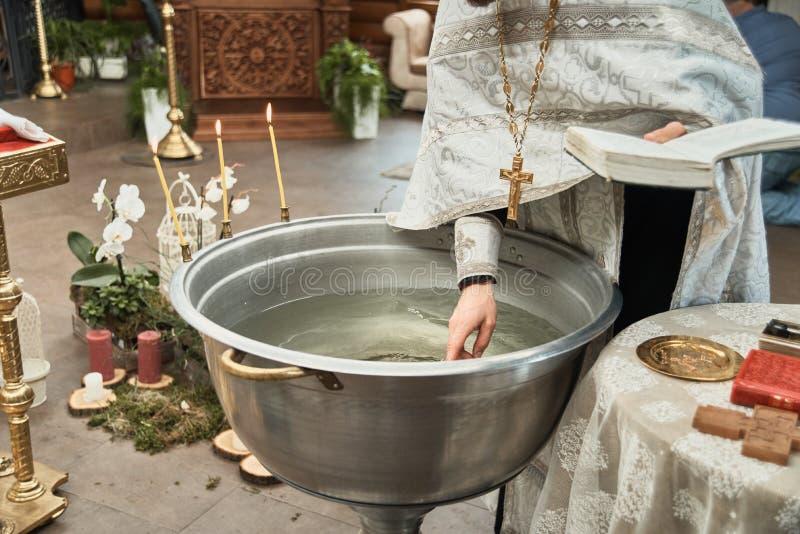 洗礼仪式在教会,教士点燃蜡烛在儿童洗礼盘 细节在正统基督教会里 库存图片