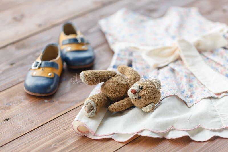 洗礼仪式婴孩` s礼服垂悬在挂衣架的-选择聚焦,拷贝空间 免版税库存图片