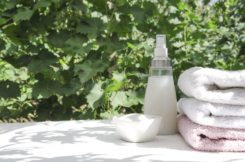 洗衣店粉末、软化剂和堆白色表面上的清洁毛巾反对绿色叶子 自然光和叶子阴影 免版税库存图片