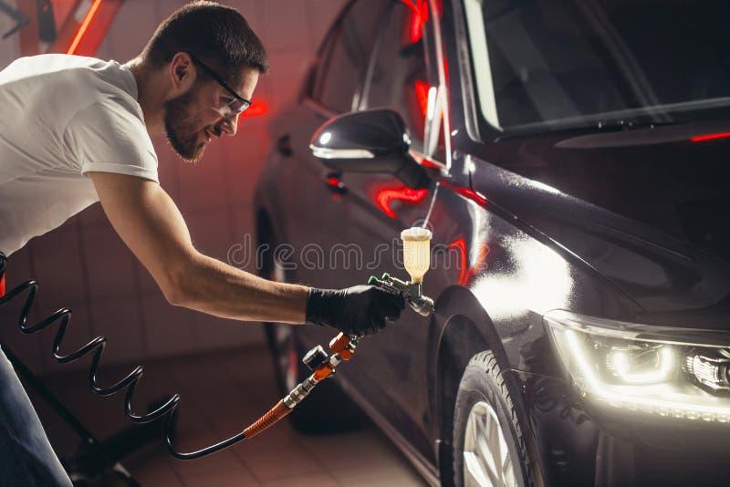 洗车和涂层事务与陶瓷涂层 对汽车的喷洒的油漆 图库摄影