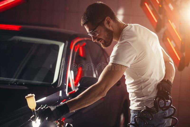 洗车和涂层事务与陶瓷涂层 对汽车的喷洒的油漆 免版税库存照片