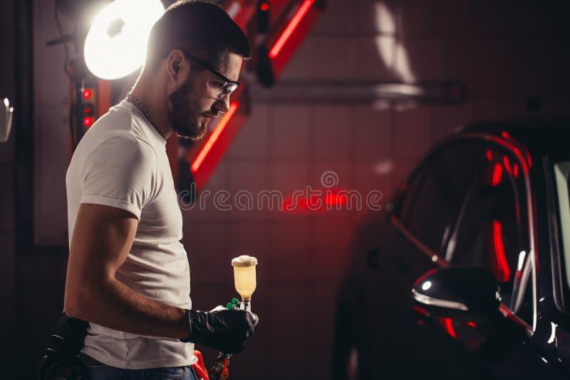 洗车和涂层事务与陶瓷涂层 对汽车的喷洒的油漆 免版税库存图片