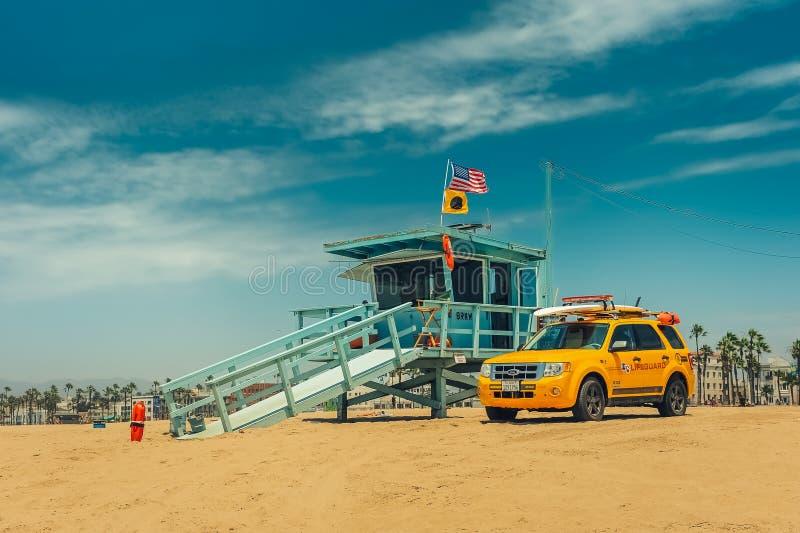 洛杉矶/California/USA - 07 22 2013年:在海滩的救生员塔与在它旁边的黄色汽车 库存图片