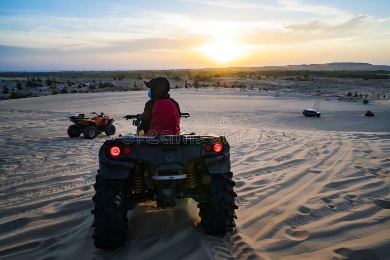 洪加达,埃及- 2018年12月10日:徒步旅行队旅行的年轻人通过驾驶ATV的埃及沙漠在日落 方形字体自行车徒步旅行队 库存图片