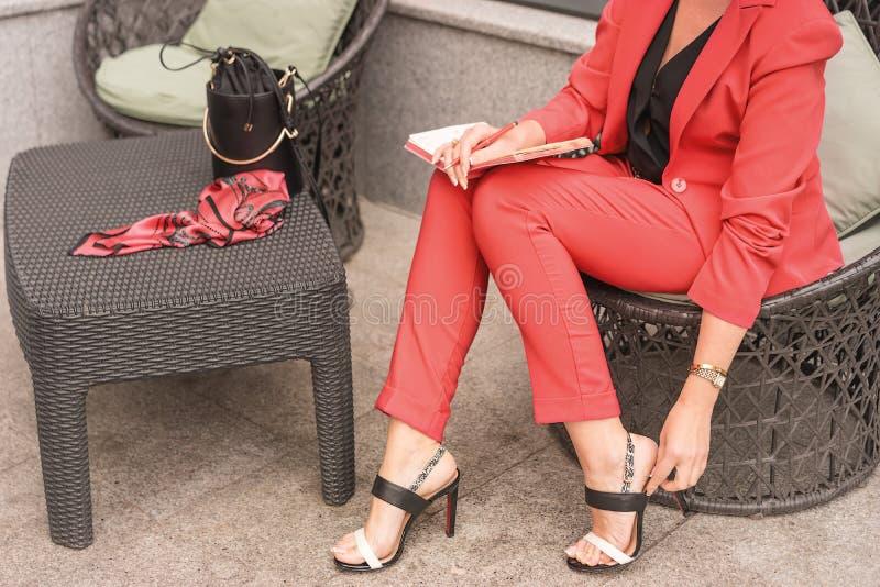 活珊瑚的颜色在凉鞋的一把椅子坐的长裤套装的妇女 在桌上的妇女前 免版税库存照片