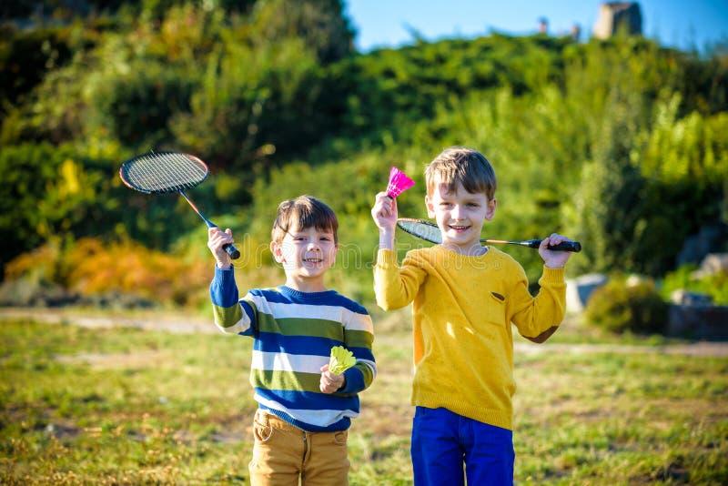活跃学龄前打在室外法院的女孩和男孩羽毛球在夏天 孩子戏剧网球 孩子的学校体育 球拍 库存图片
