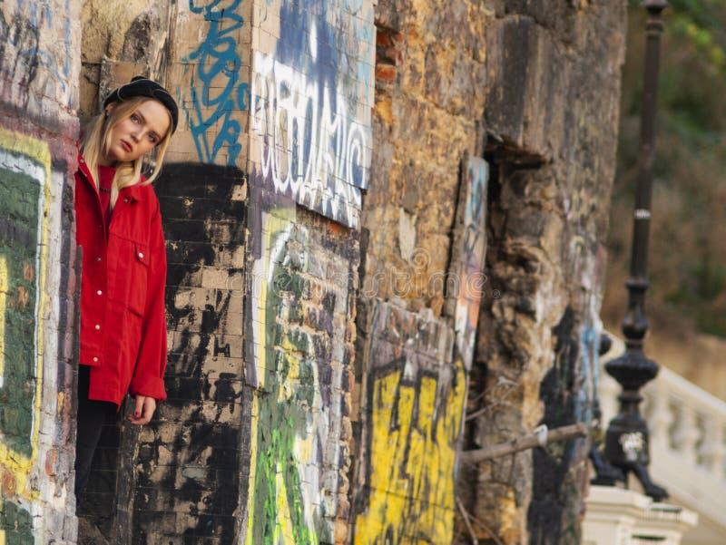 活跃少女白肤金发的行家在与墙壁的废墟附近站立在街道画 免版税库存照片