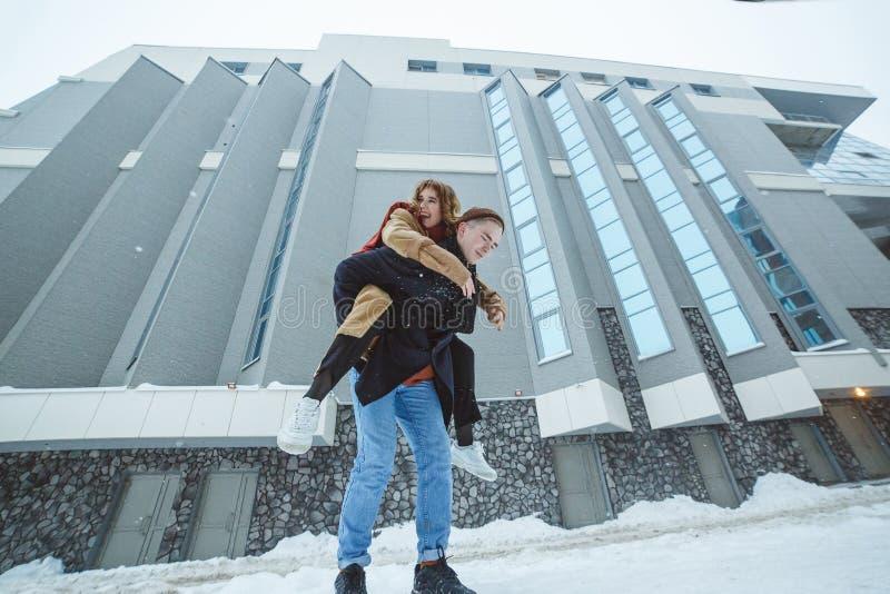 活跃年轻夫妇赛跑,一起跳跃和享用在冬天城市背景中 库存照片